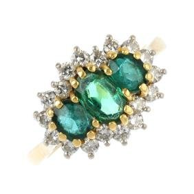 An 18ct gold emerald and diamond dress ring. The