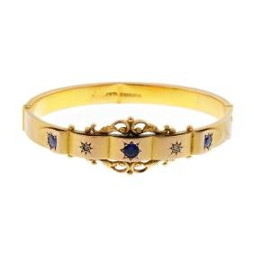An Edwardian 9ct gold paste and diamond bangle. The