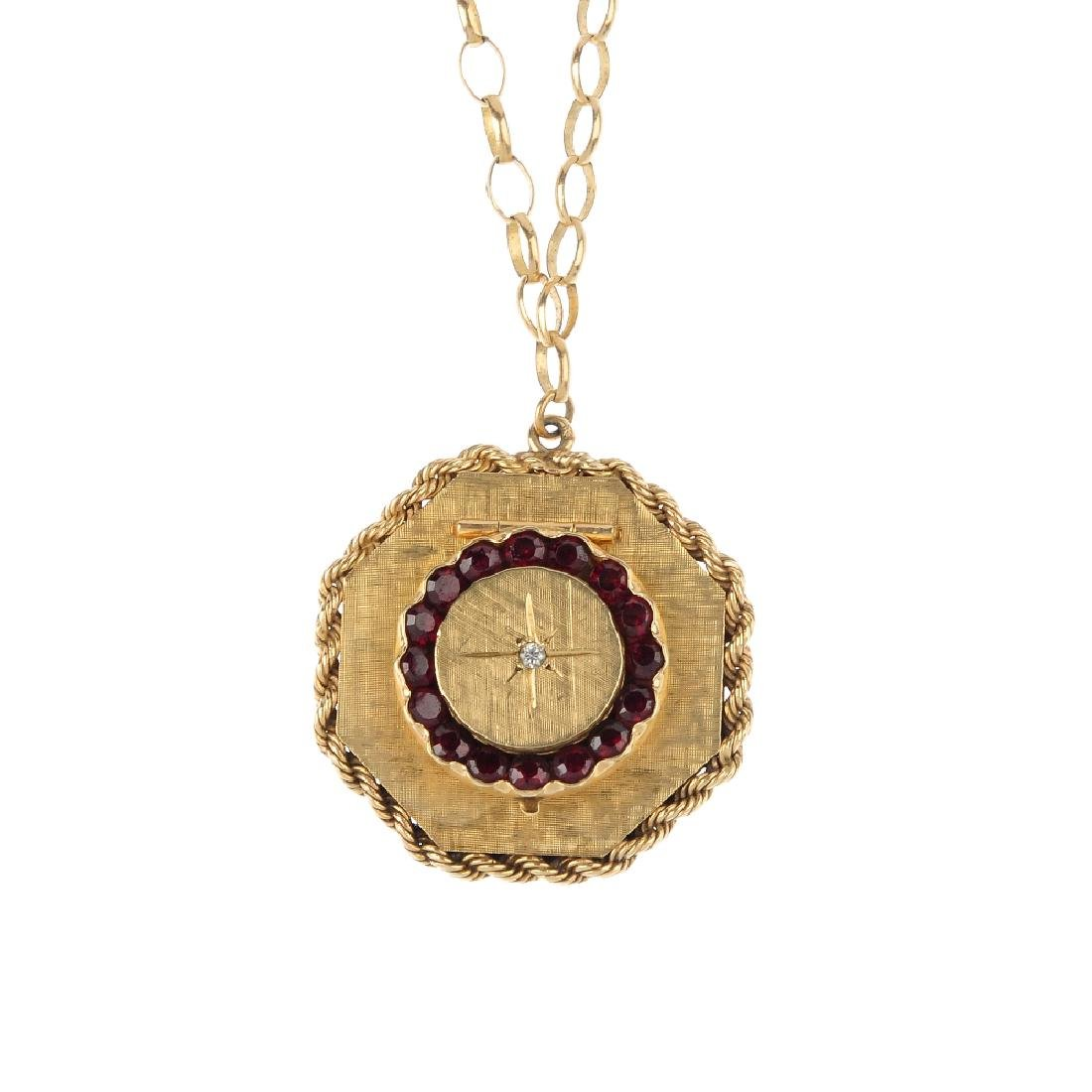 A gem-set locket. Of hexagonal outline, the textured