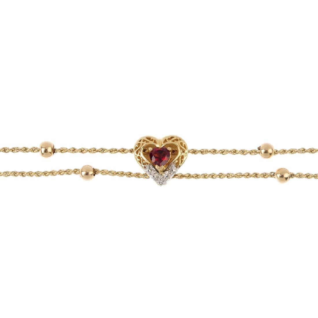 A garnet bracelet. Of bi-colour design, the heart-shape