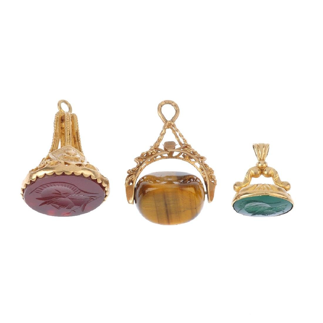 Three 9ct gold hardstone fobs. To include a carved