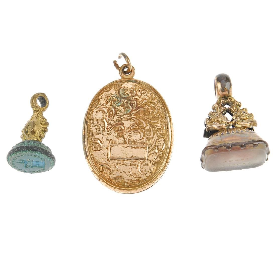 Two fobs and a locket. The locket of oval outline with