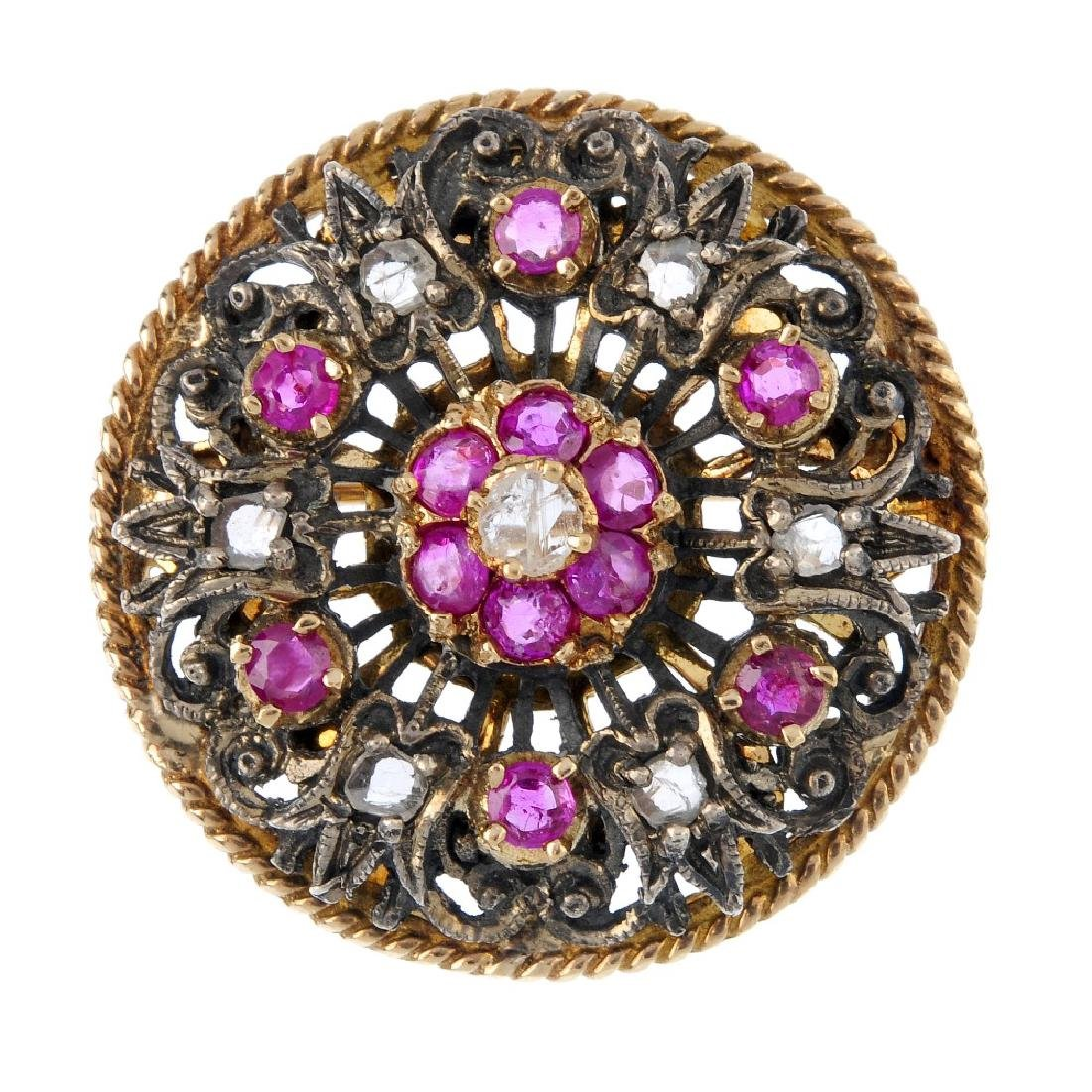 A diamond and ruby floral brooch. Of openwork design,