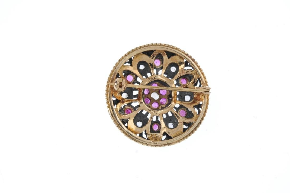 A diamond and ruby floral brooch. Of openwork design, - 2