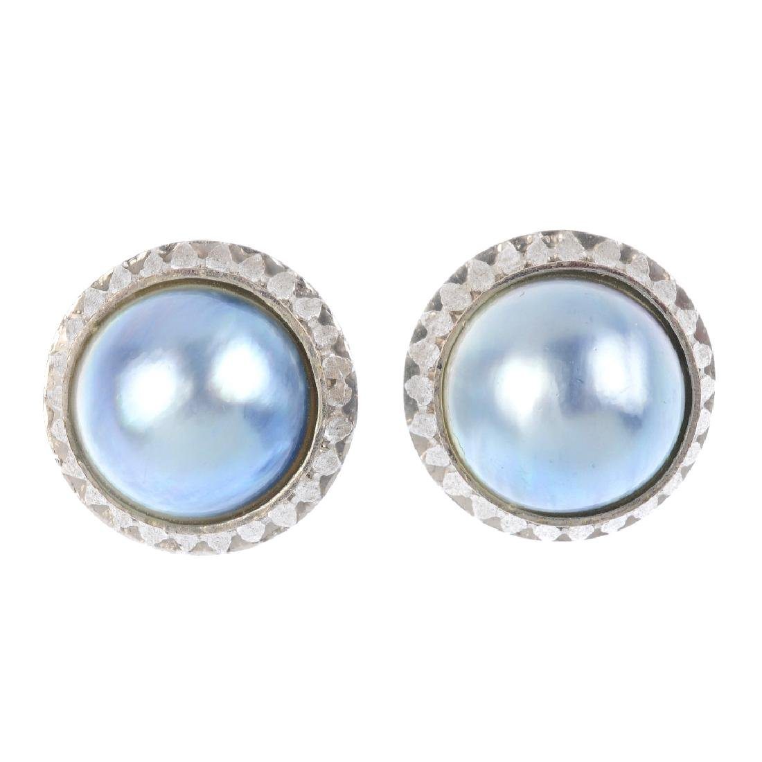 A pair of mabe pearl earrings. Each designed as a