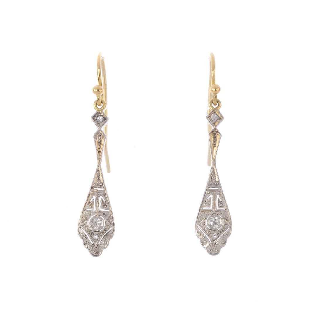 A pair of diamond earrings. Each designed as an old and