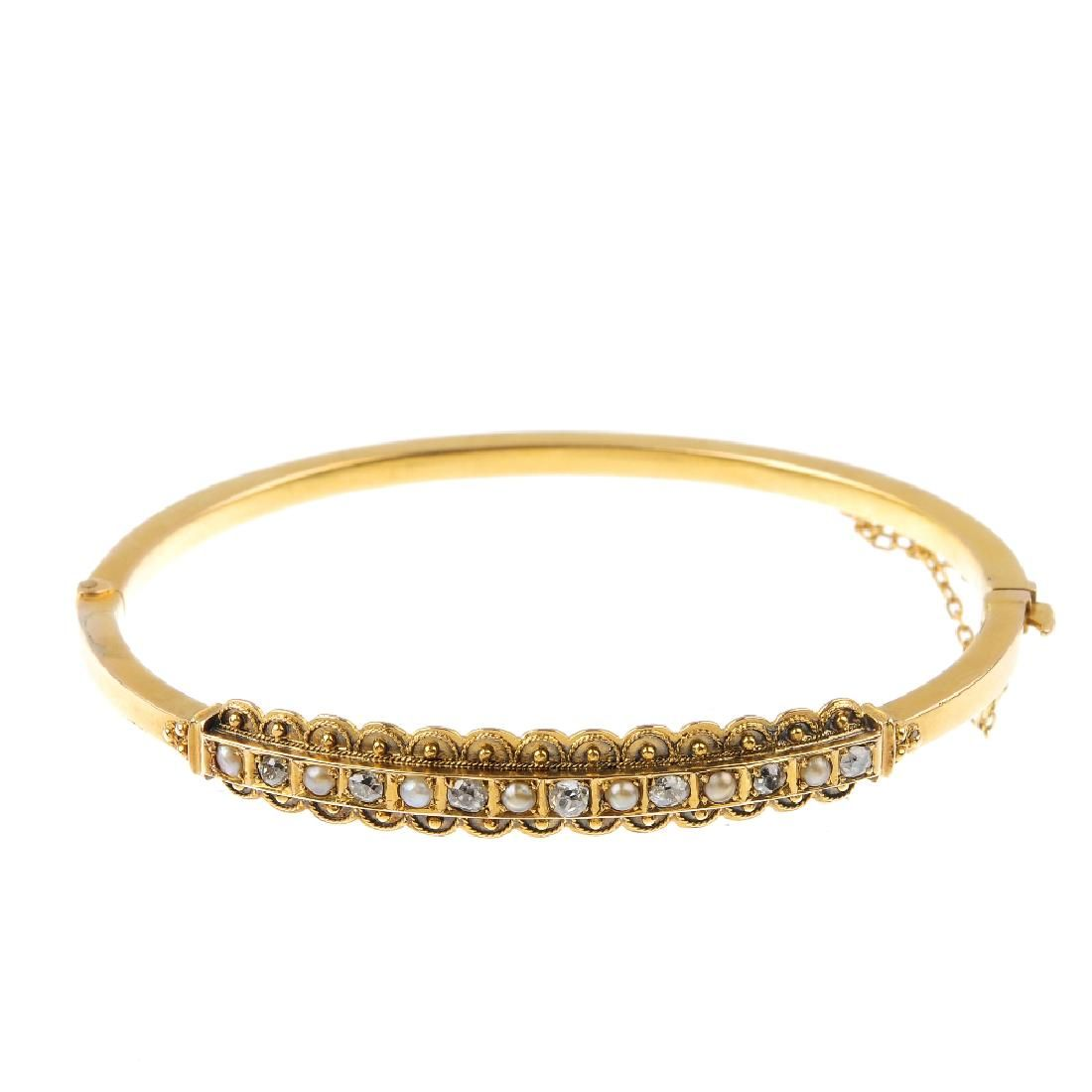 A late Victorian gold split pearl and diamond bangle