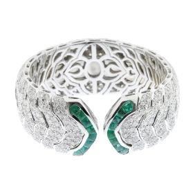 An 18ct gold diamond and emerald cuff bangle. The