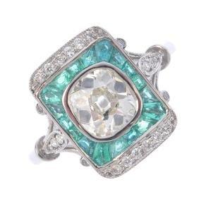 A diamond and emerald dress ring. The old-cut diamond