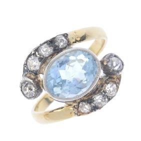 An aquamarine and diamond crossover ring. The