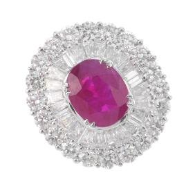 A ruby and diamond cocktail ring. The oval-shape ruby,