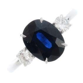 A sapphire and diamond three-stone ring. The oval-shape