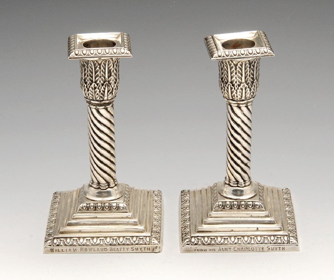 A pair of late Victorian silver mounted candlesticks,