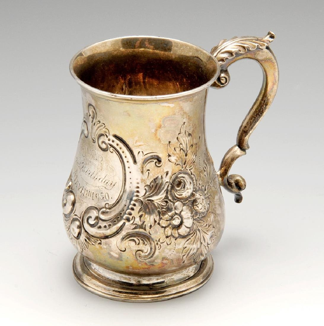 A Victorian silver mug, the baluster form florally