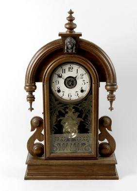 A group of wall and mantel clocks. The first an