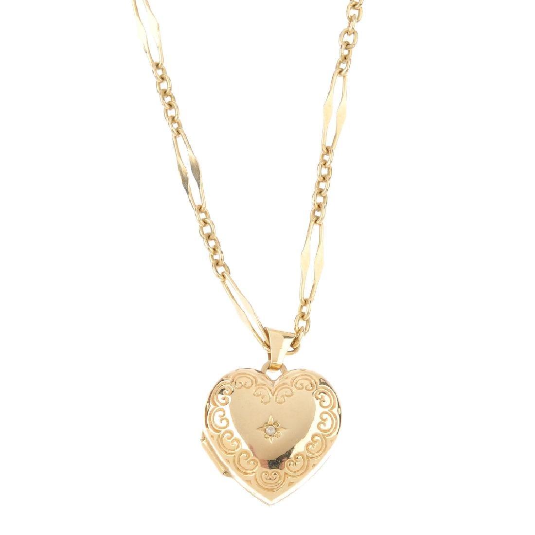 A 9ct gold diamond heart locket. The single-cut