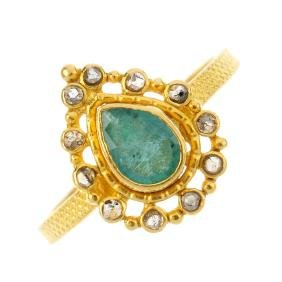 An emerald and diamond cluster ring. The pear-shape