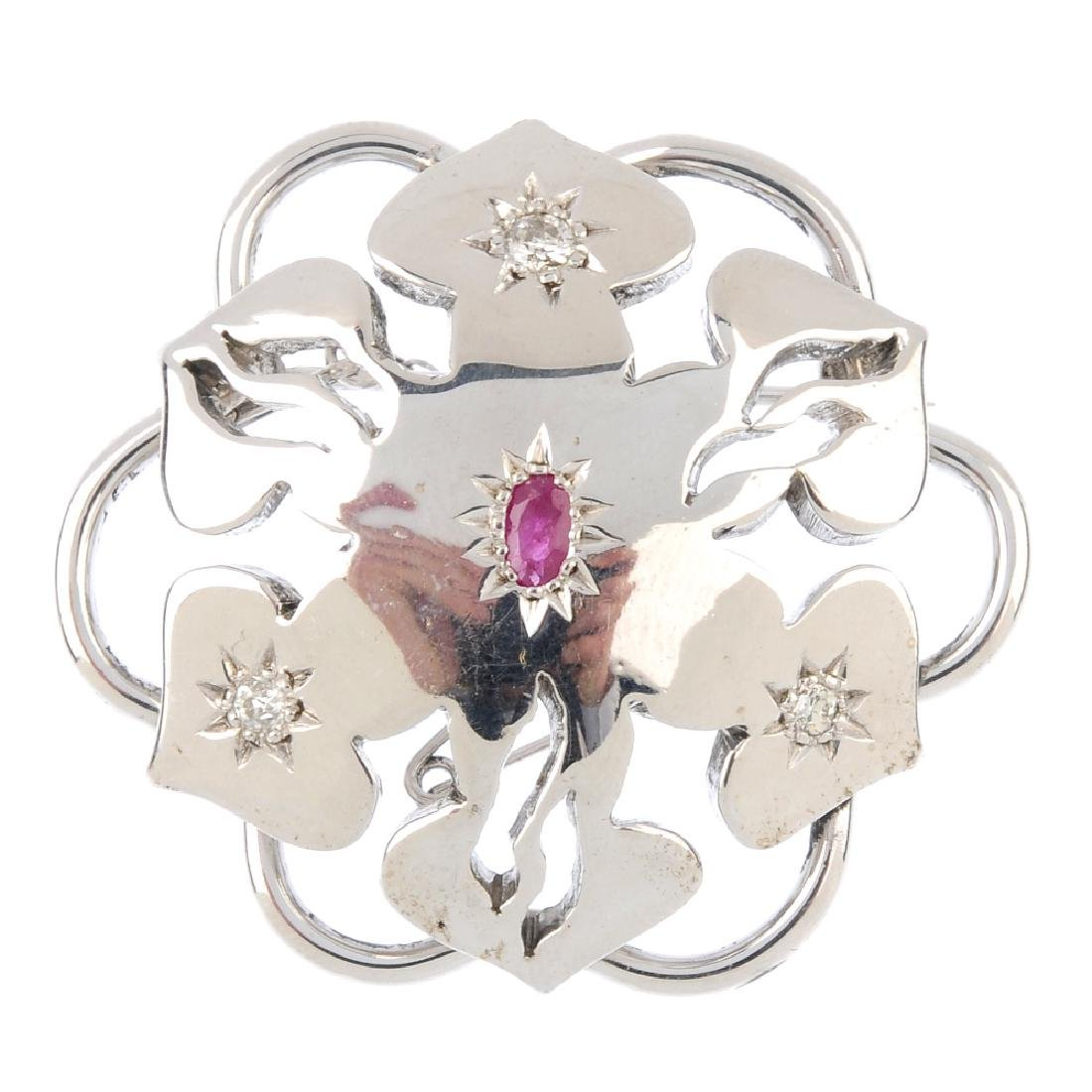 A diamond and ruby brooch. Of stylised floral design,