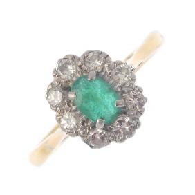 An 18ct gold emerald and diamond cluster ring. The