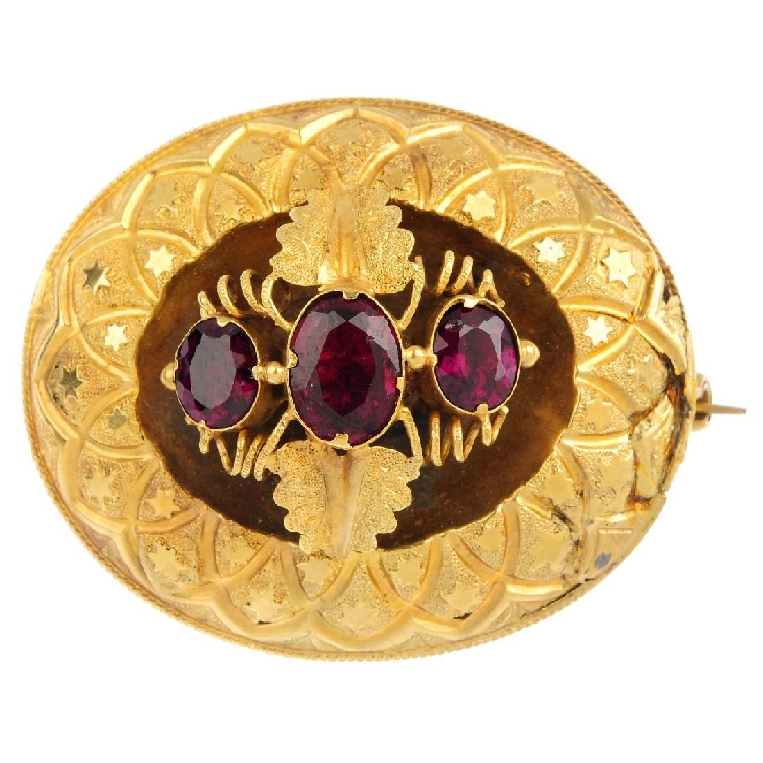 A mid Victorian gold garnet brooch. Comprising three
