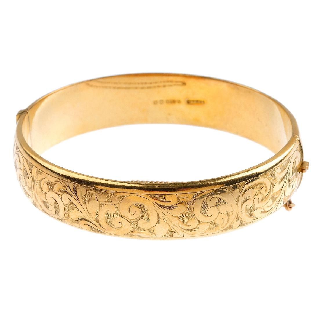 A mid 20th century 9ct gold hinged bangle. With
