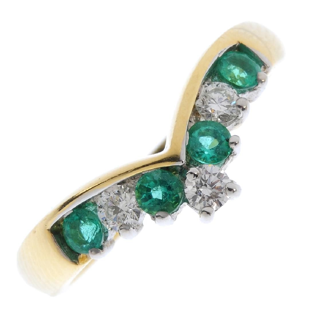 An 18ct gold emerald and diamond ring. The