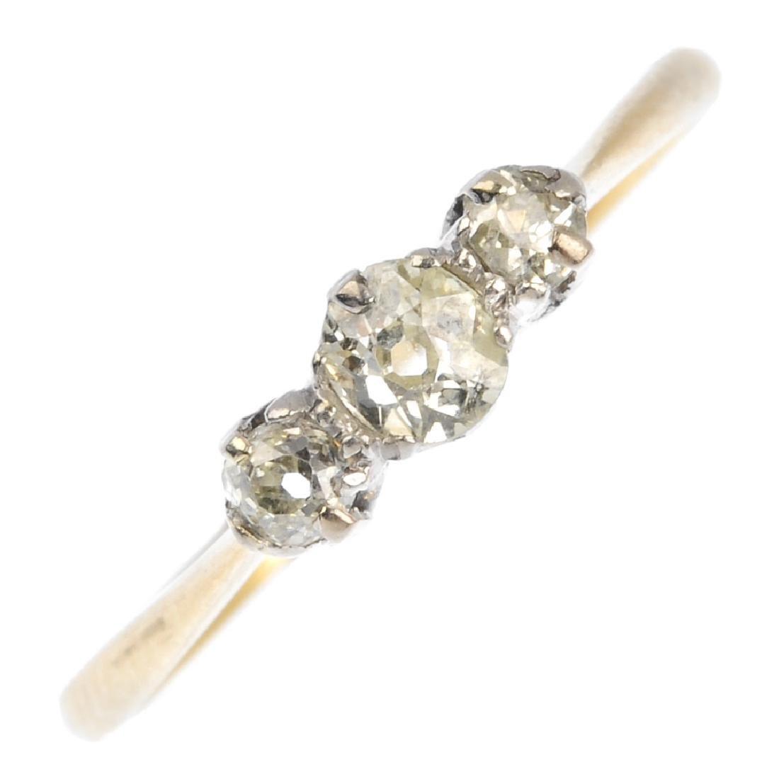 A diamond three-stone ring. The old-cut diamond line,