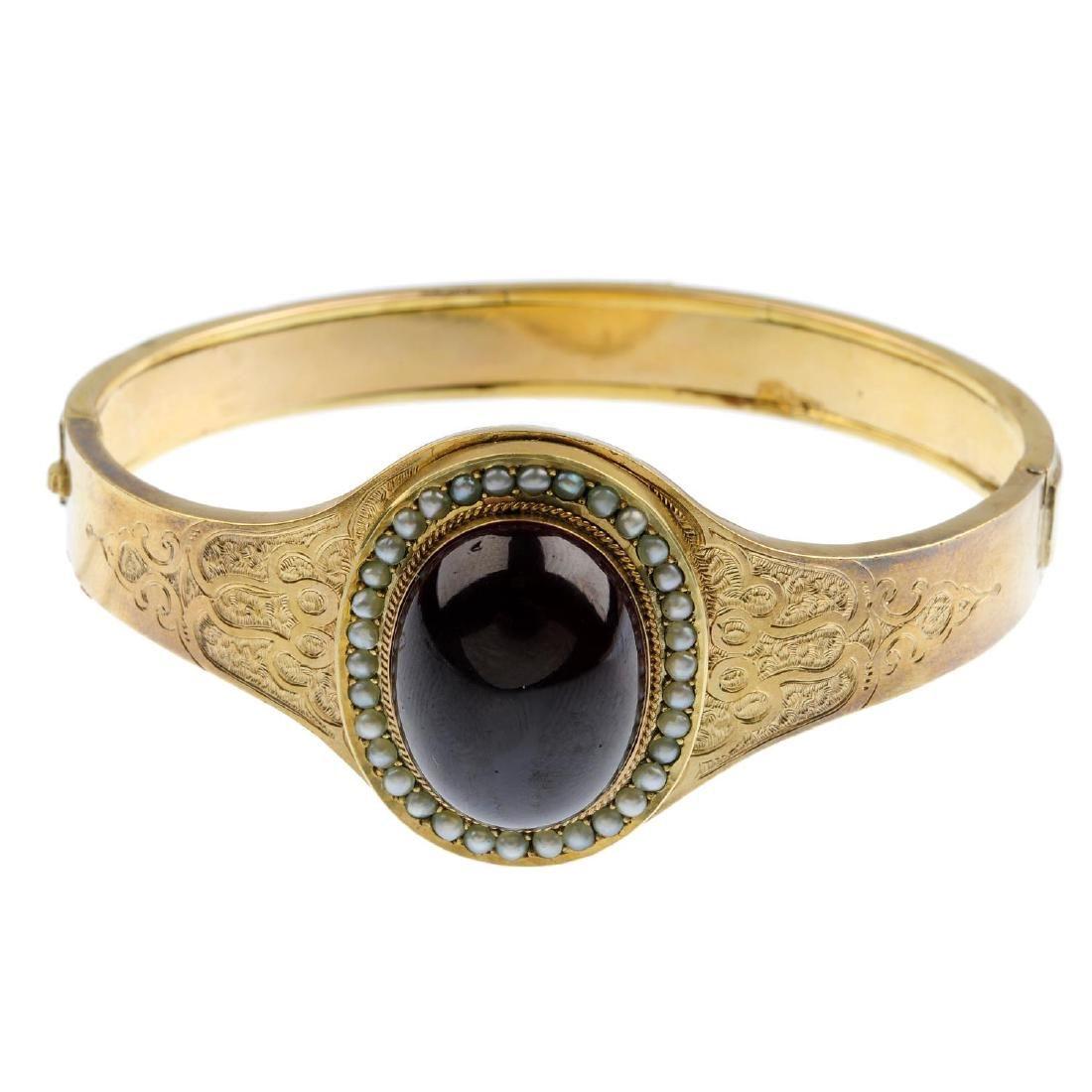 A late Victorian garnet and seed pearl hinged bangle.