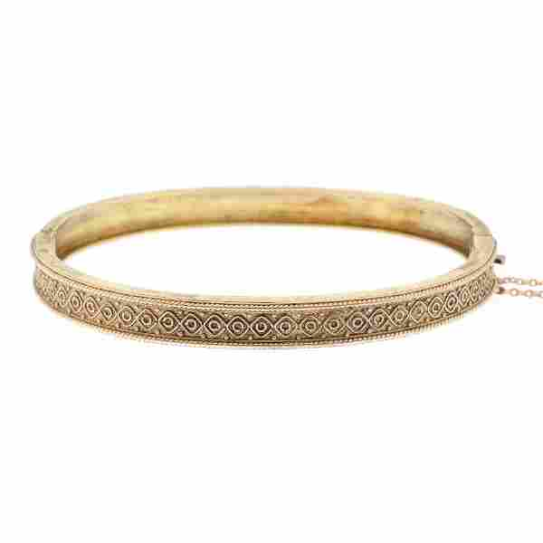 A late Victorian 9ct gold hinged bangle. The front