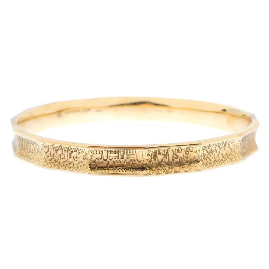 A 9ct gold bangle. Of faceted design, with engine