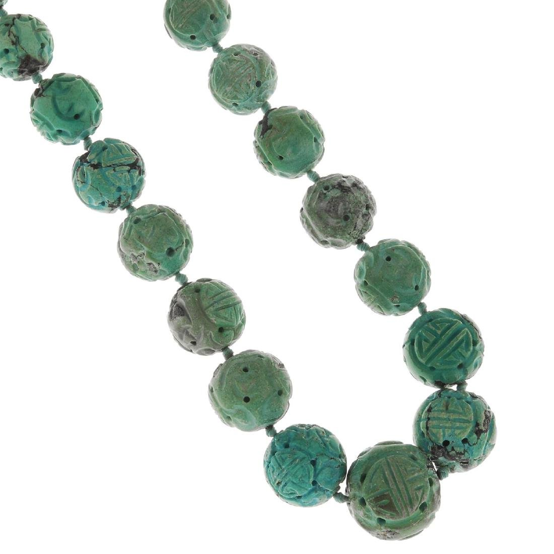 A Chinese Shou carved turquoise bead necklace.