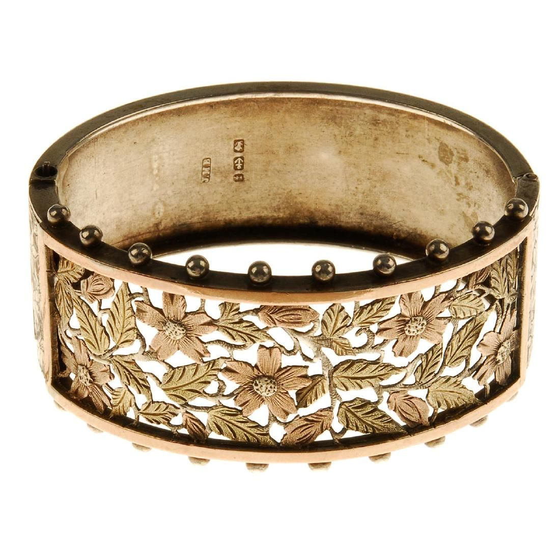 A late Victorian silver hinged bangle. The openwork