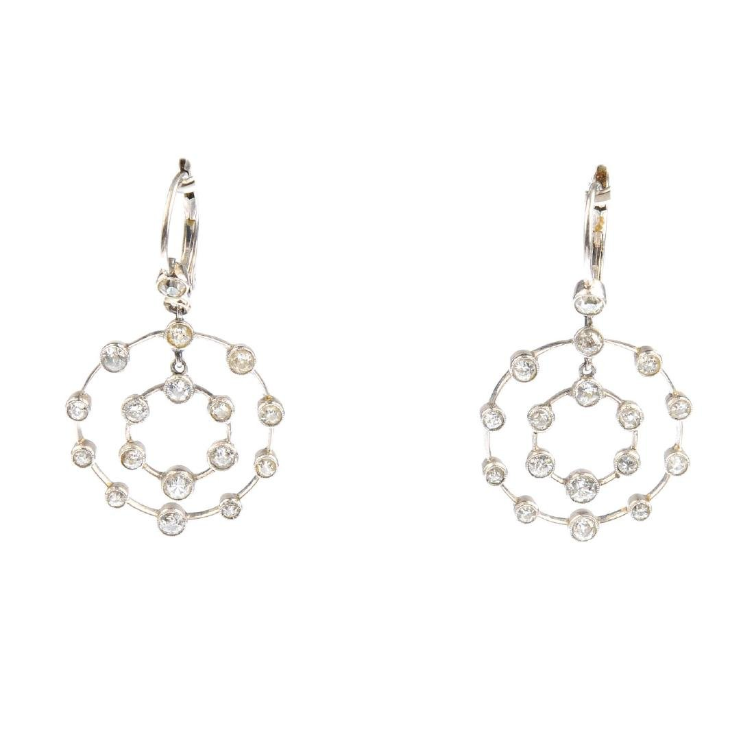 A pair of diamond earrings. Each designed as two