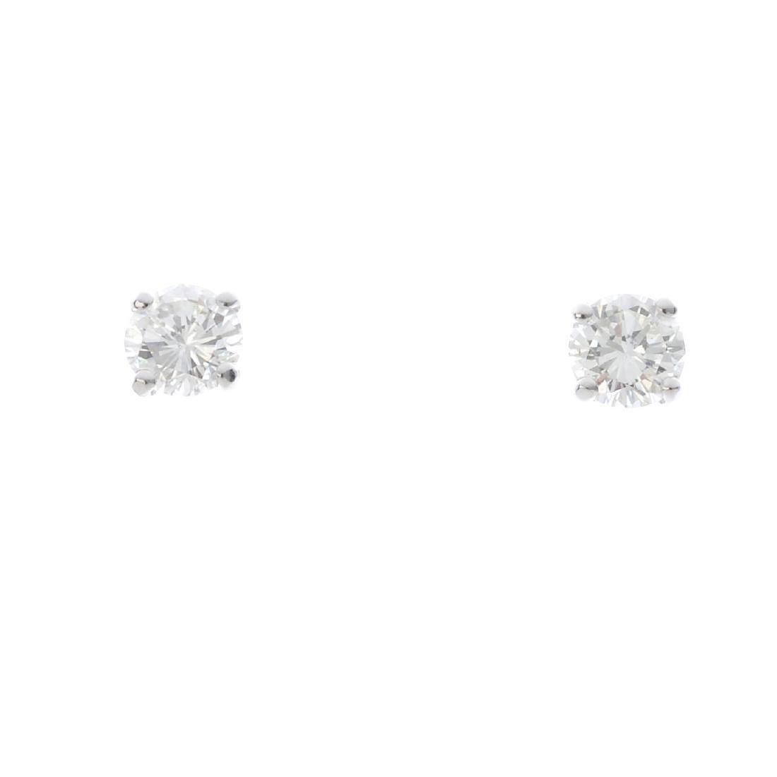 A pair of brilliant-cut diamond stud earrings. Total