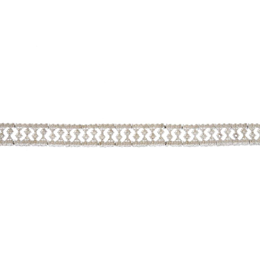 A 9ct gold diamond bracelet. Of openwork design, the