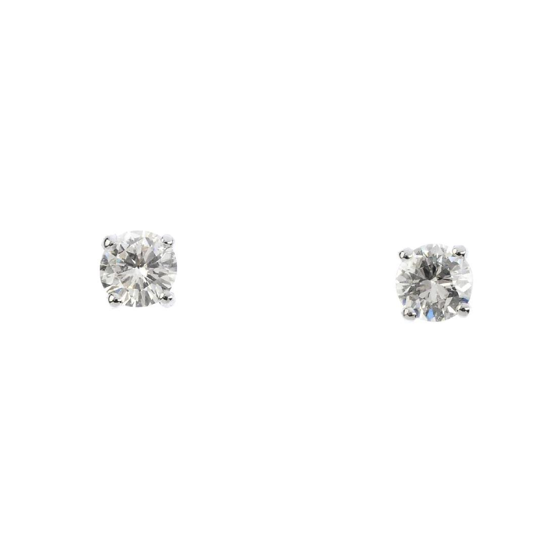 A pair of diamond stud earrings. Each designed as a