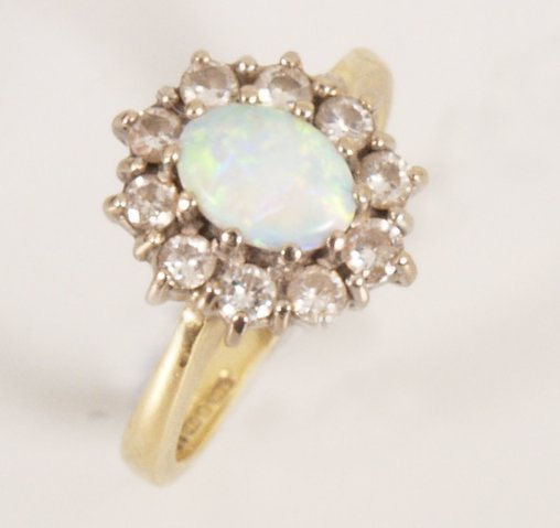 11: 18ct gold oval opal and diamond eleven stone cluste