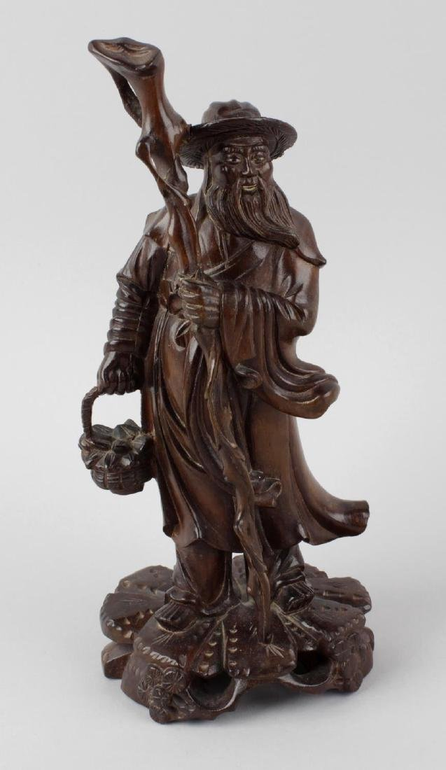 An Oriental carved rootwood figure of an elder. Circa