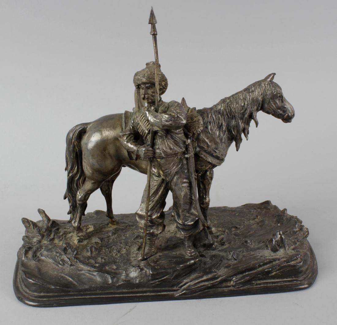 A base metal figure group of a cossack and horse.