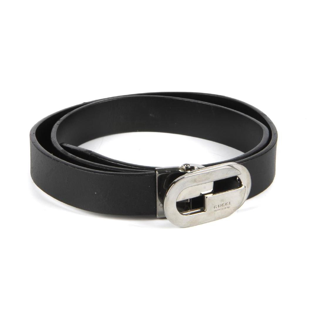 GUCCI - a black leather belt. Featuring a polished