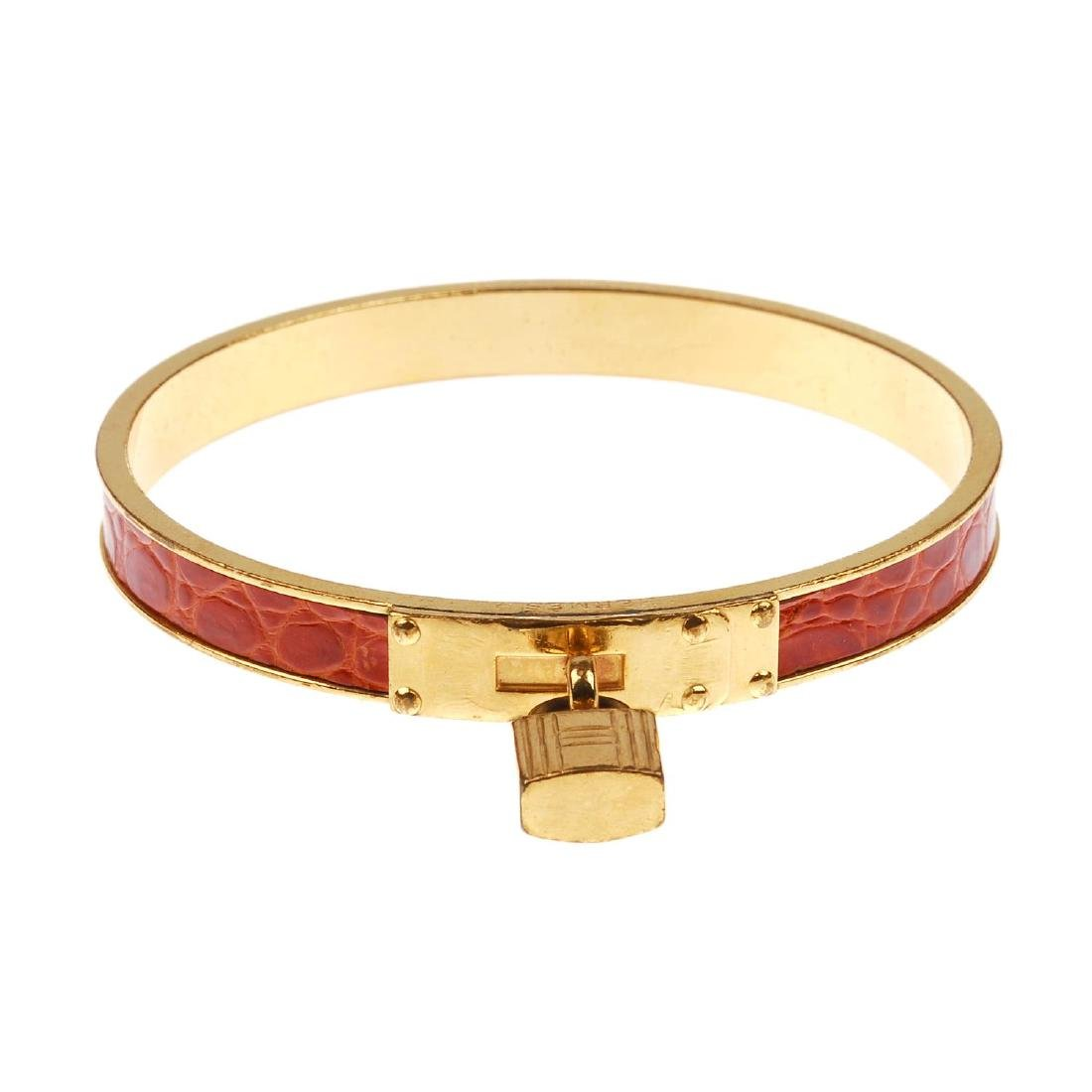 HERMÈS - a Kelly bangle. The circular gold-tone bangle
