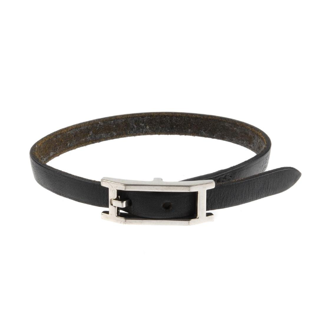 HERMÈS - a black leather bracelet. The silver-tone