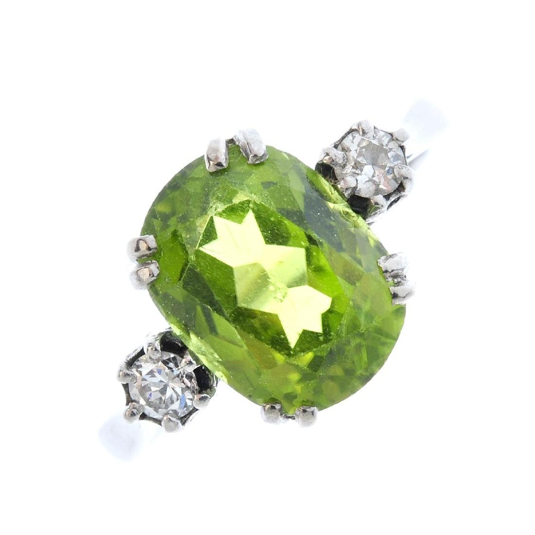 A peridot and diamond ring. The cushion-shape peridot,