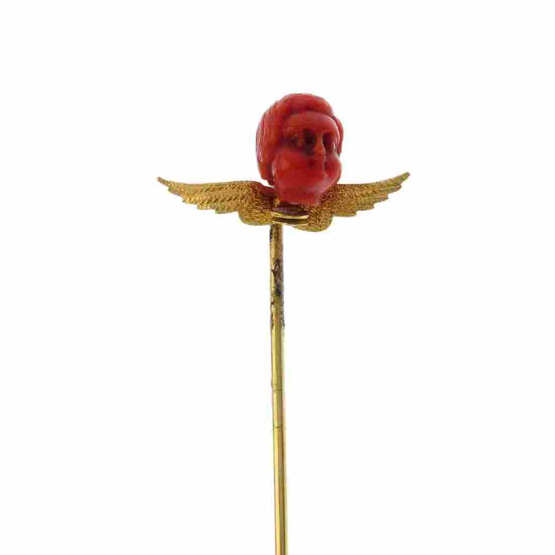 A late Victorian gold coral stickpin. The carved coral