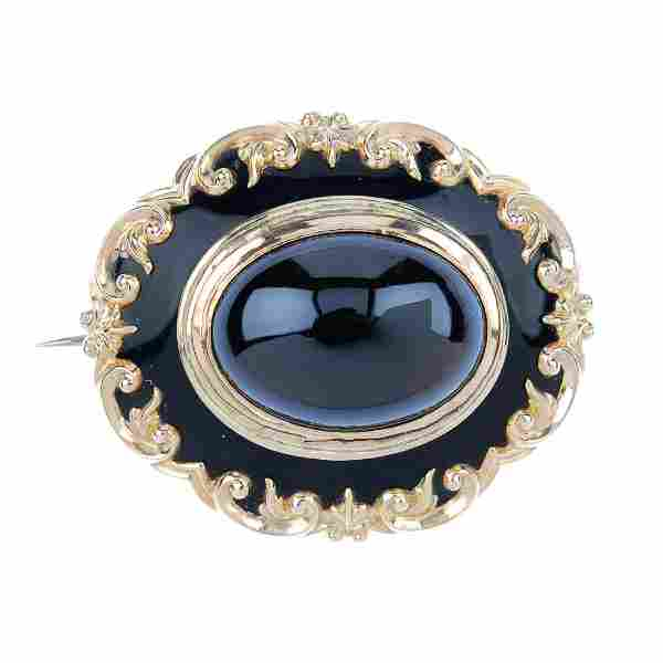 A late Victorian gold garnet cabochon brooch. Of oval