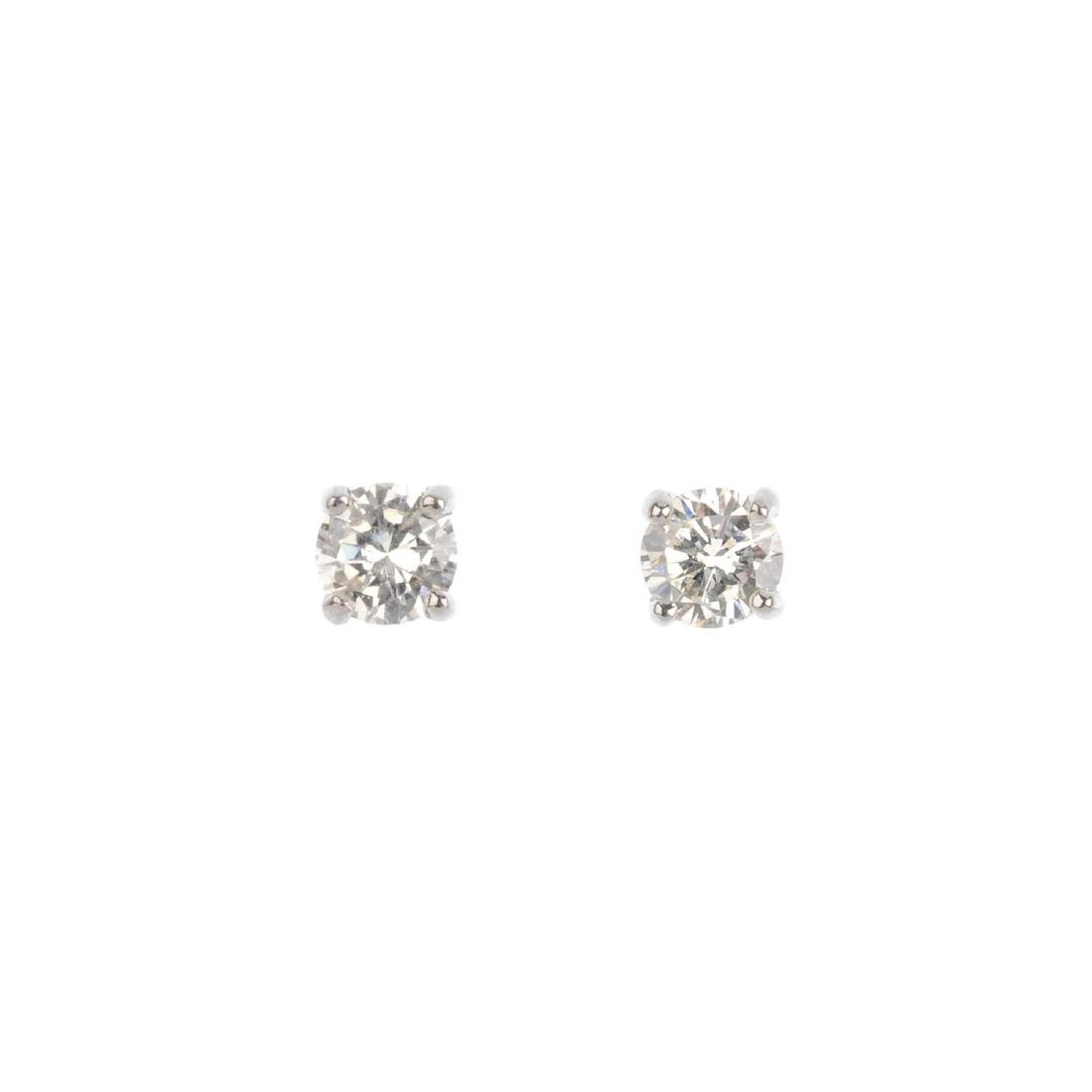 A pair of brilliant-cut diamond stud earrings. Total