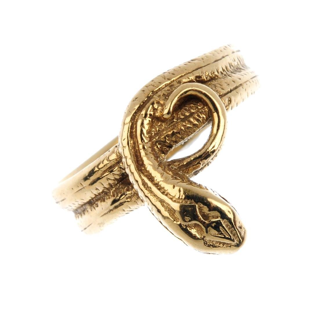 A 9ct gold snake ring. Designed as a coiled snake, with