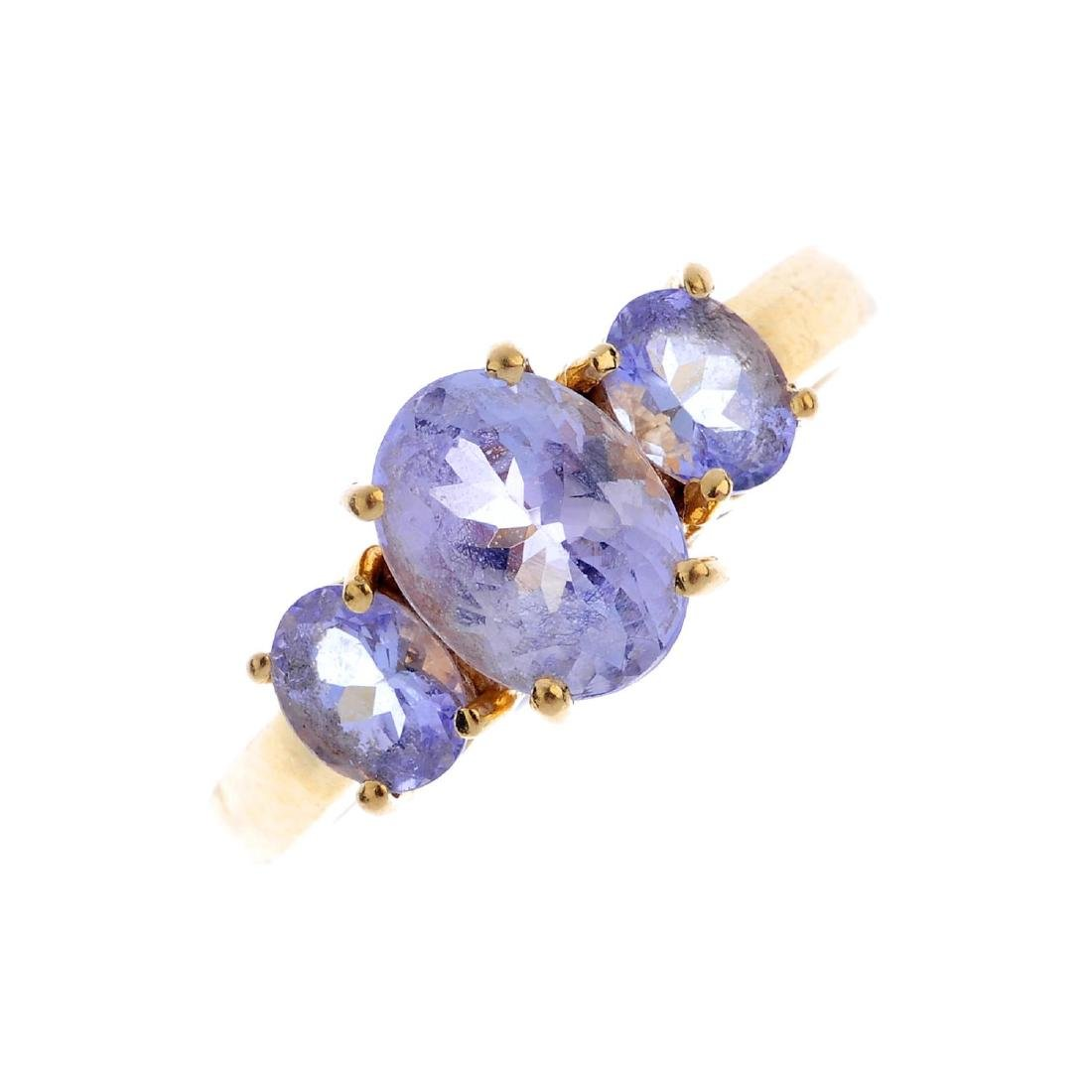 An 18ct gold tanzanite three-stone ring. The oval-shape