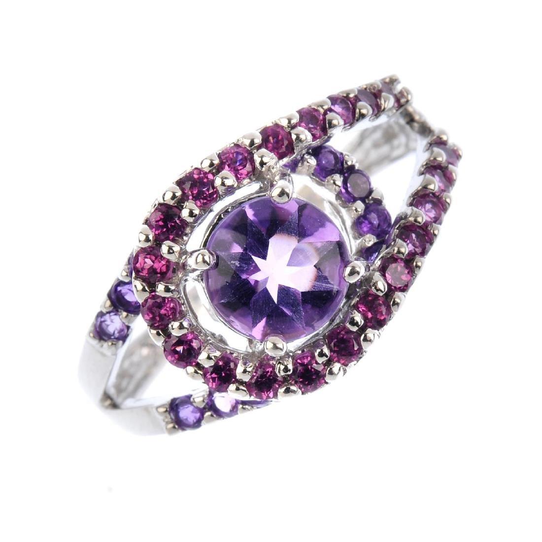 An amethyst dress ring. The fancy-cut circular-shape