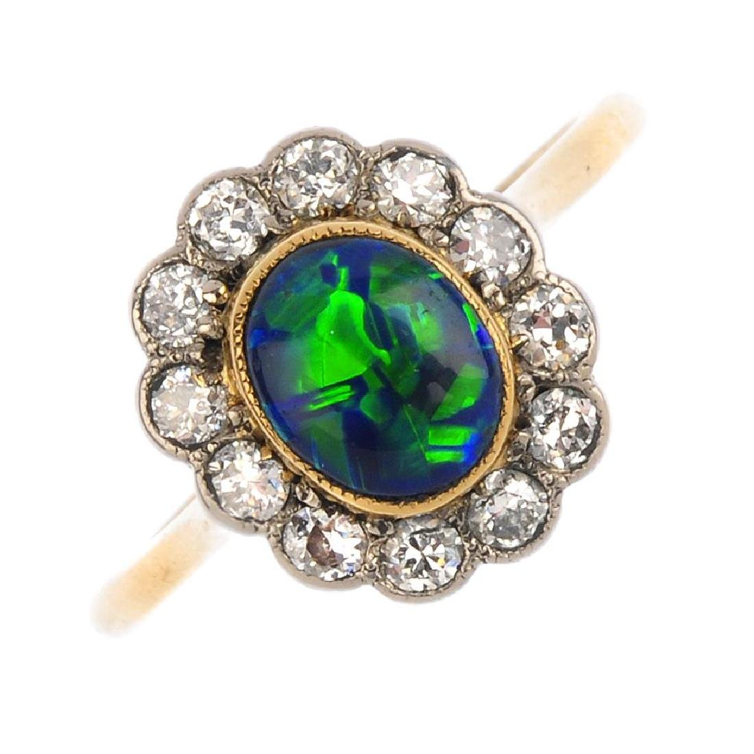 A black opal and diamond cluster ring. The oval opal